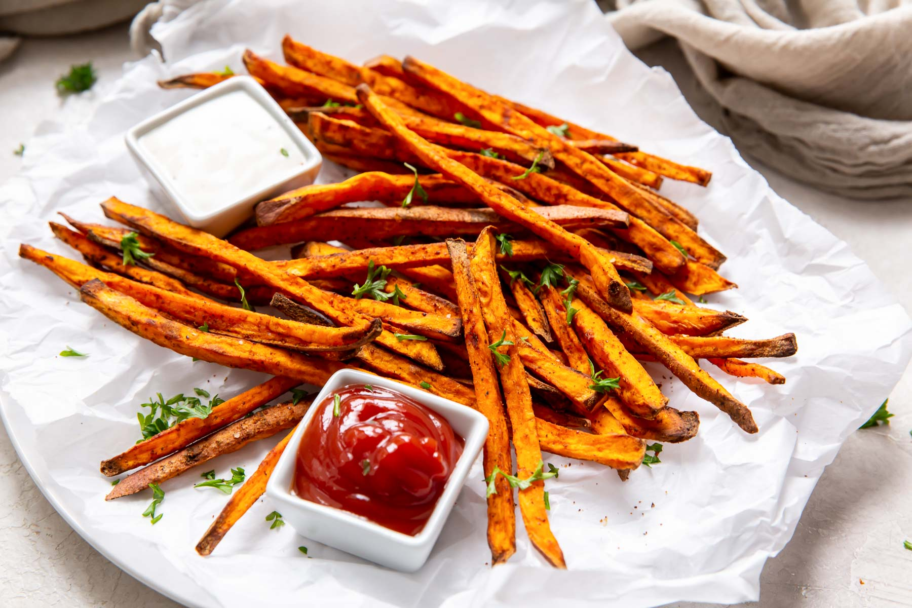fries on a parchment paper lined plate, with a dish of ketchup and ranch