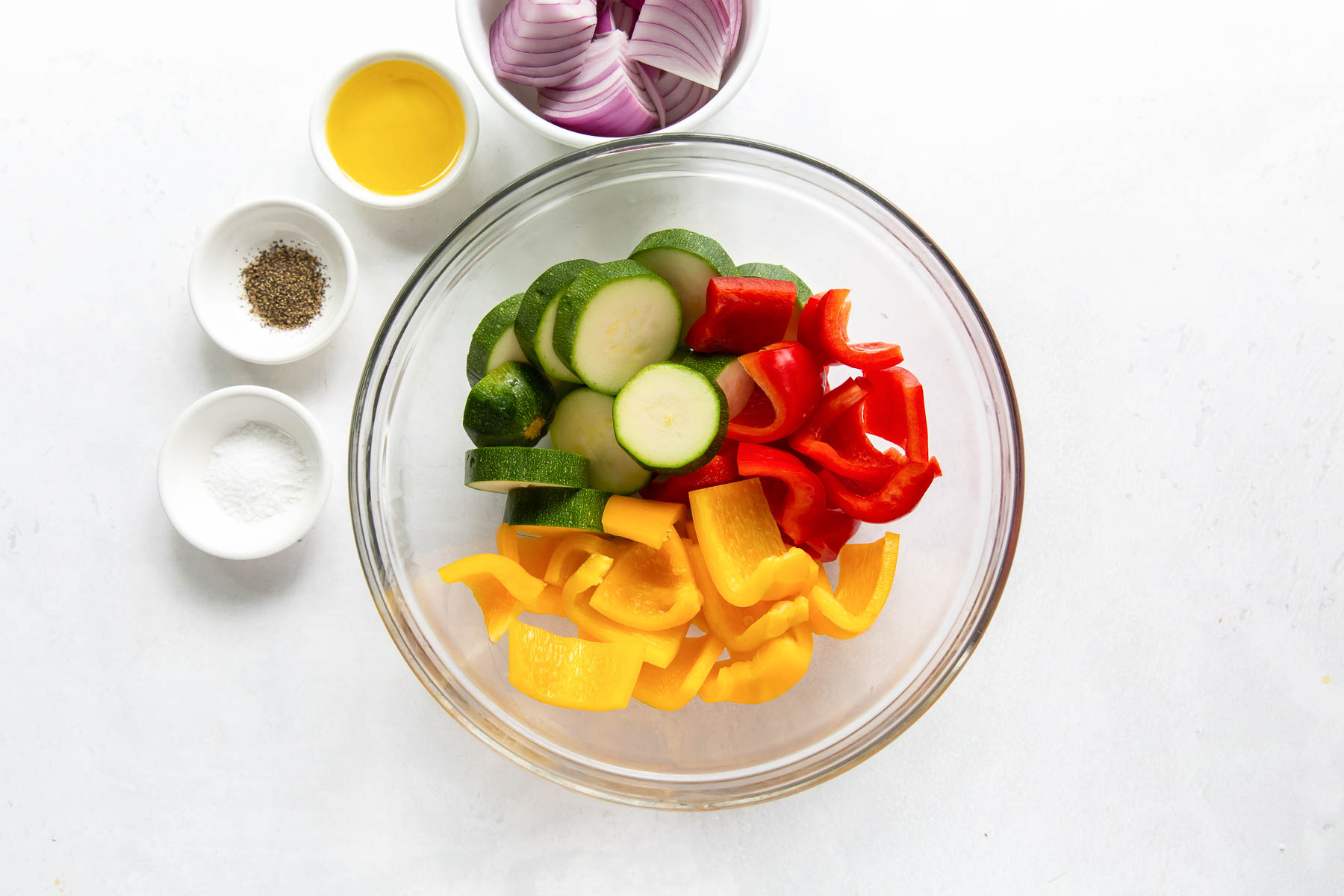 zucchini and bell peppers in a bowl with olive oil, salt, pepper and onion on the side