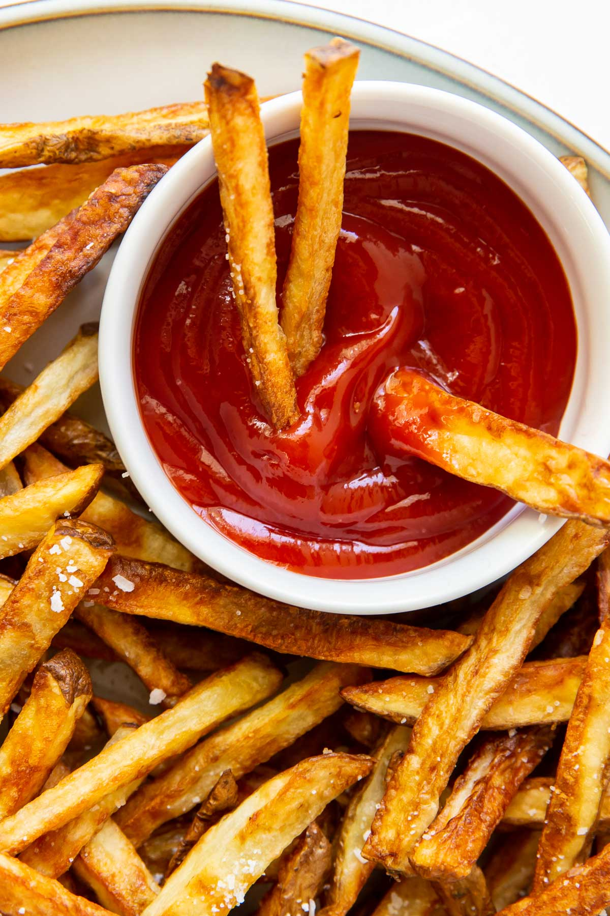 close up of three air fryer french fries in a dish of ketchup with more fries around the dish