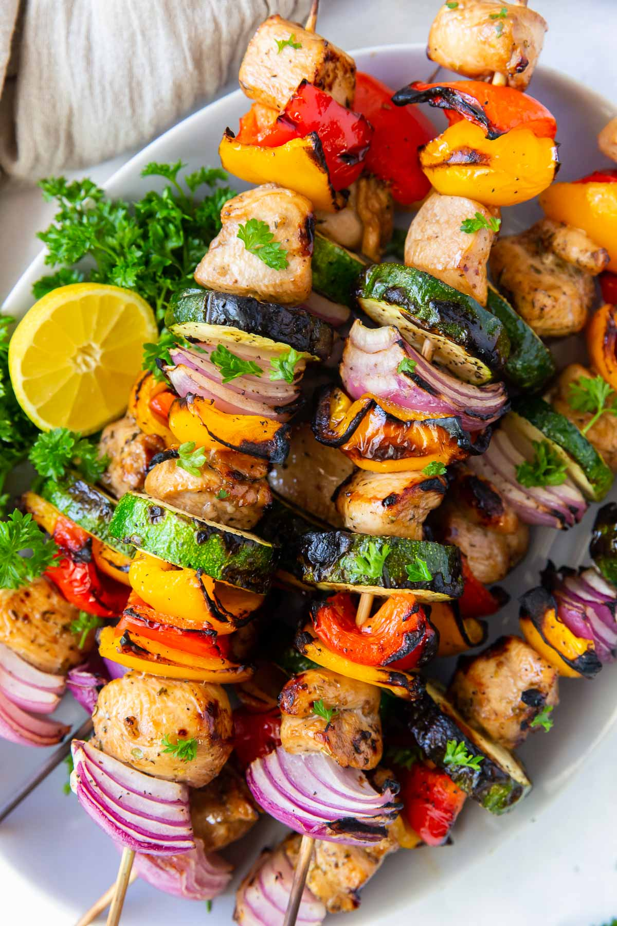 grilled chicken kabobs with vegetables stacked on a plate