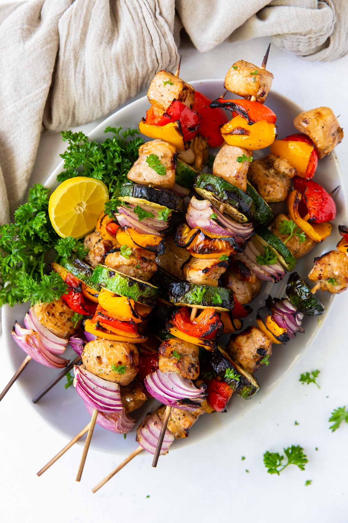 grilled kabobs with chicken and vegetables stacked on a plate with lemon and parsley garnish