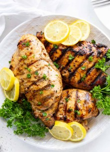 three marinated grilled chicken breasts on a plate with lemon slices and parsley