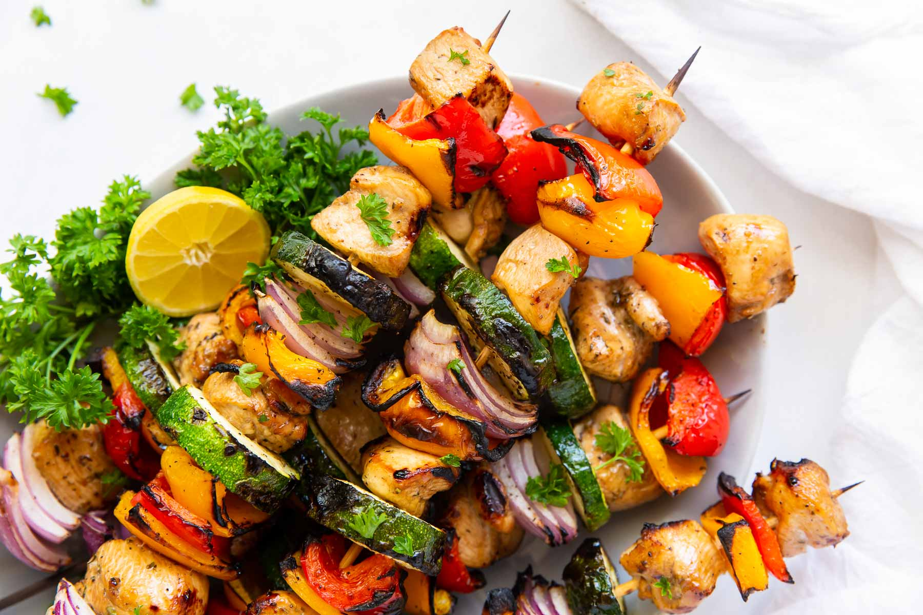 cooked shish kabobs with grilled chicken, red onion, bell peppers and zucchini stacked on a plate