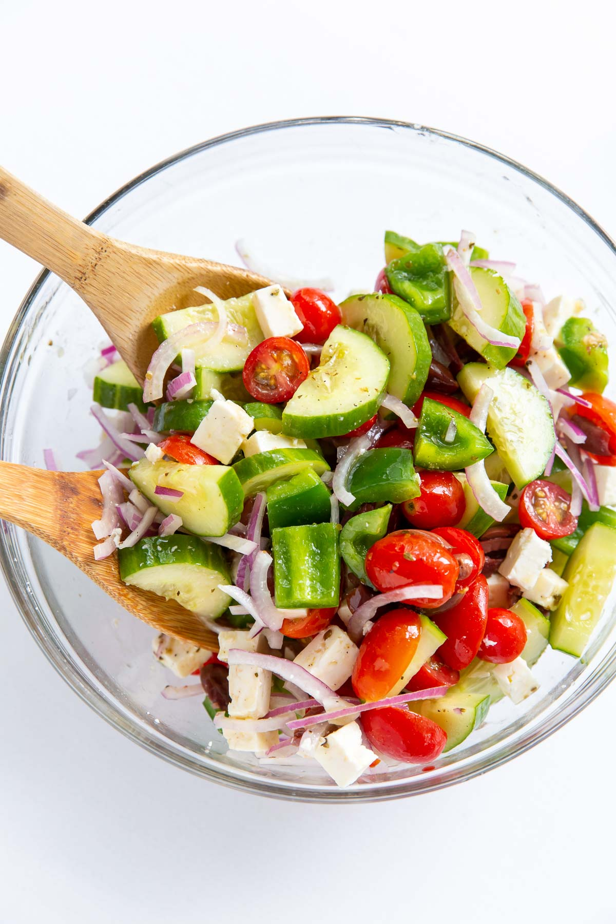 greek salad tossed with dressing in a glass bowl with wooden salad servers