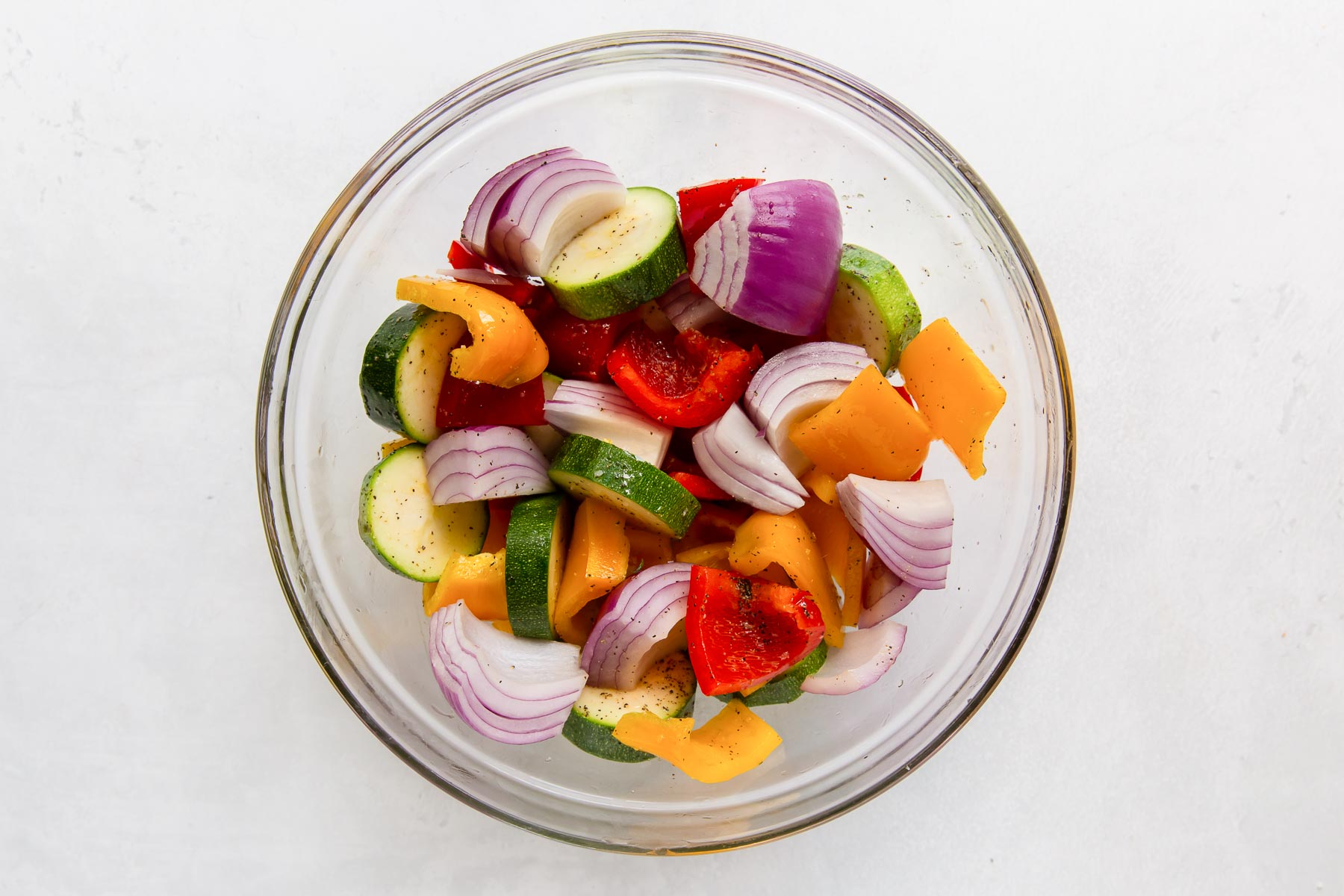 chopped zucchini, bell peppers and red onion in a bowl, tossed with olive oil, salt and pepper