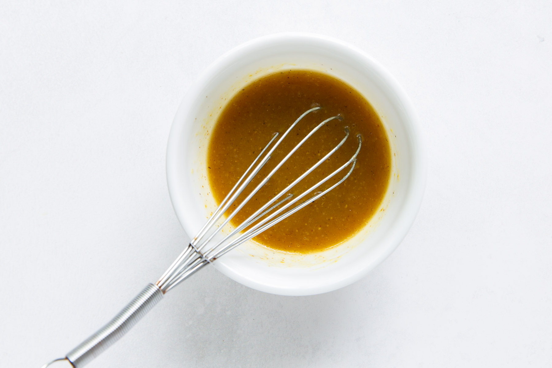 whisked dressing in a small white bowl with a whisk