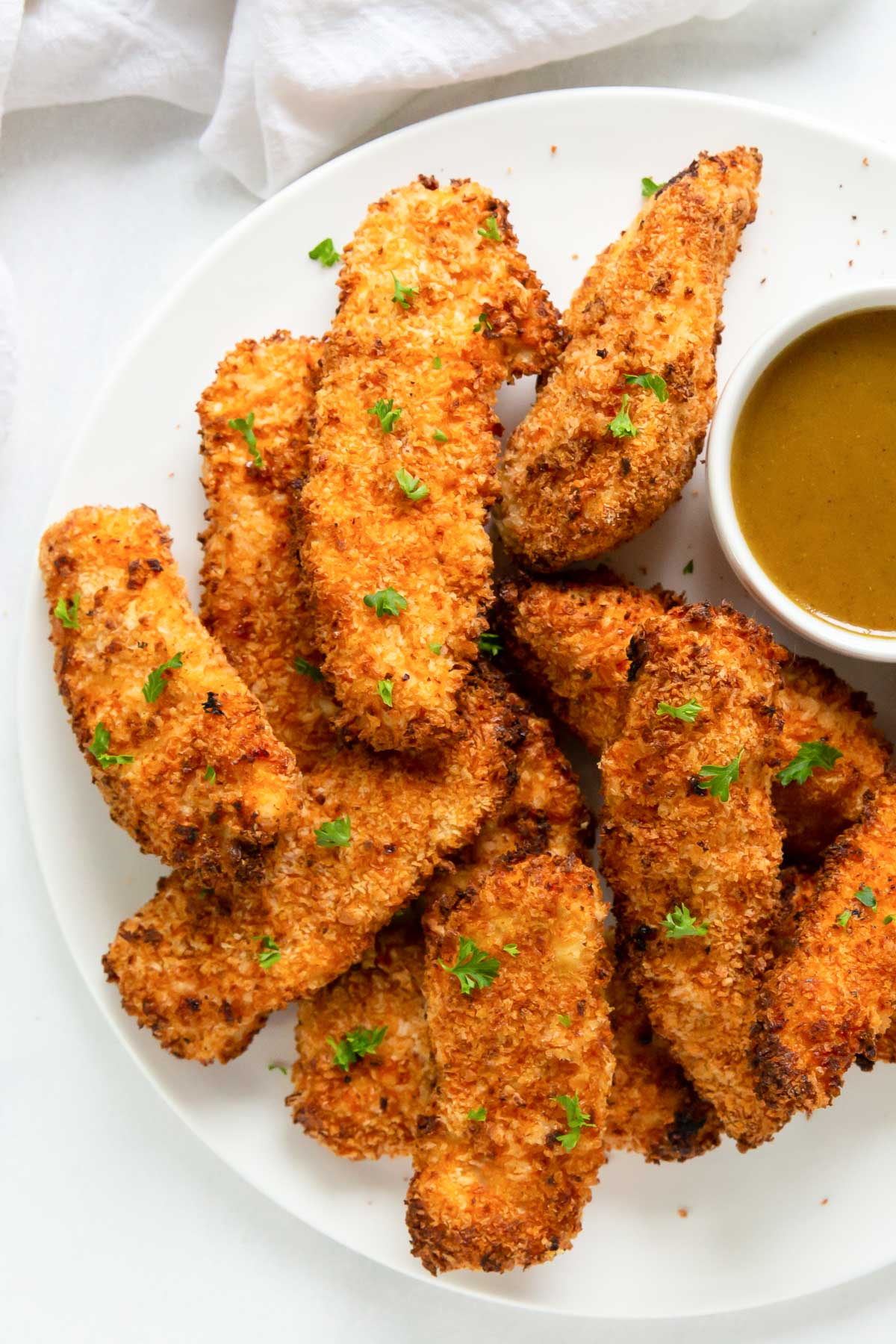 air fryer chicken tenders stacked on a plate with a dish of honey mustard sauce