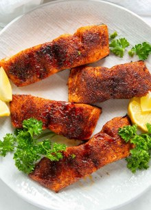 four air fried salmon fillets on a plate with parsley and lemon slices