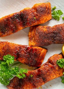 four air fryer salmon fillets on a plate with parsley garnish