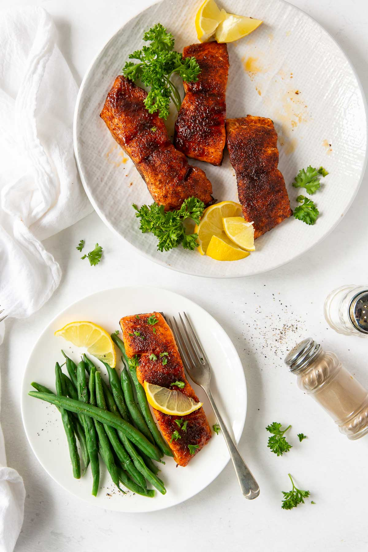 air fryer salmon served with green beans with a plate of three salmon fillets in background