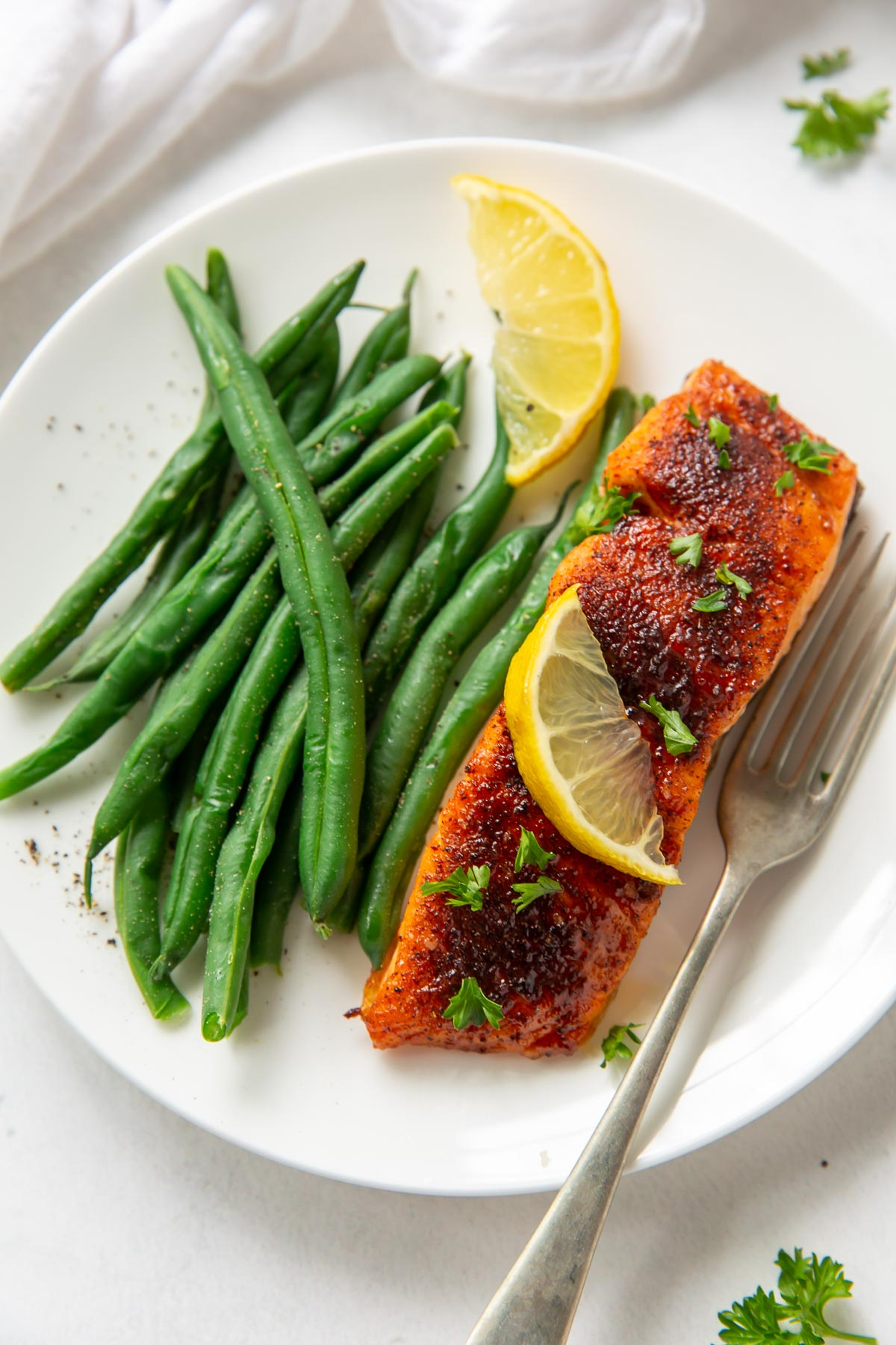 air fryer salmon fillet served with green beans and lemon slices