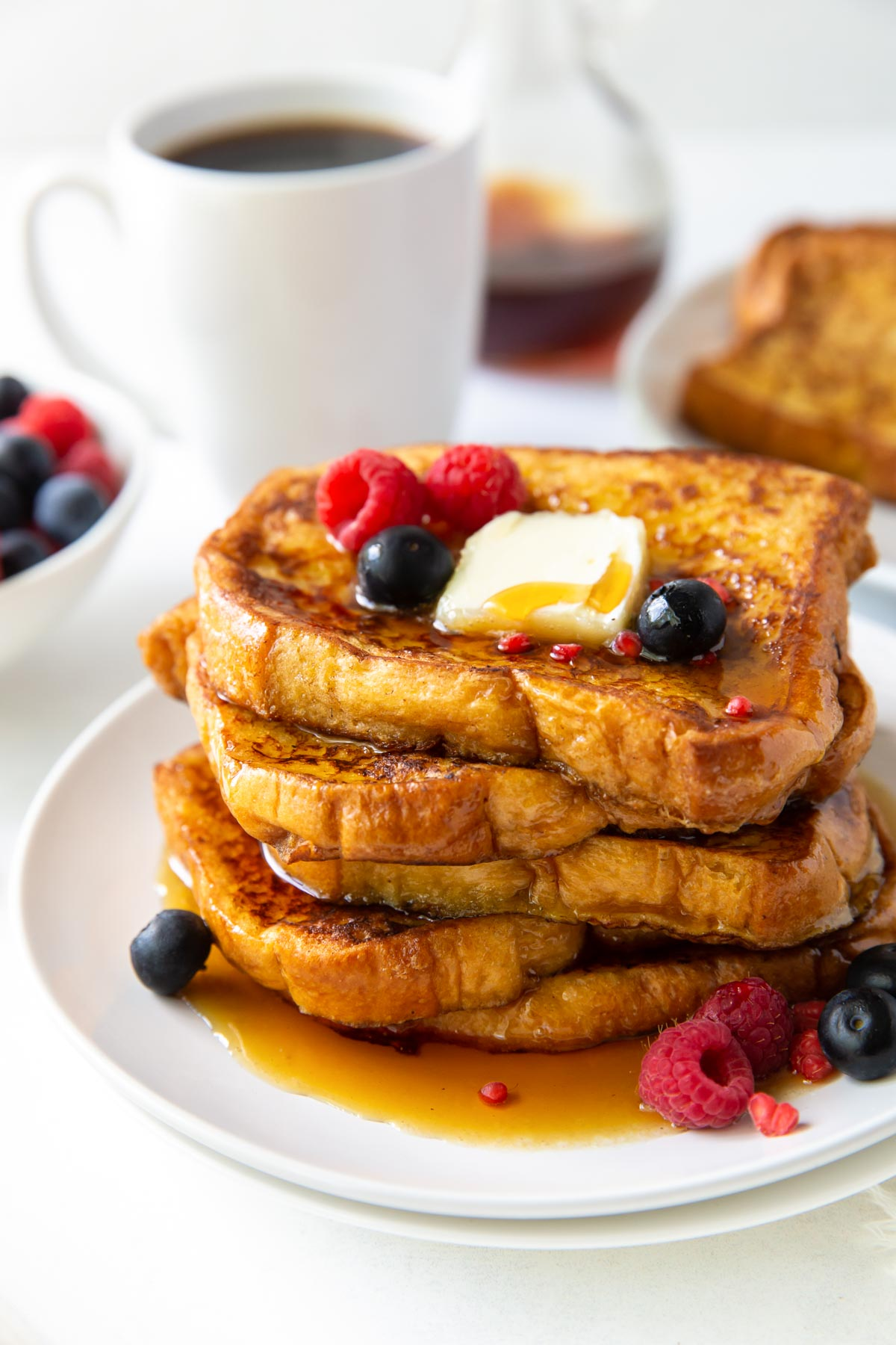 five slices of french toast stacked on a plate and served with butter, berries and maple syrup