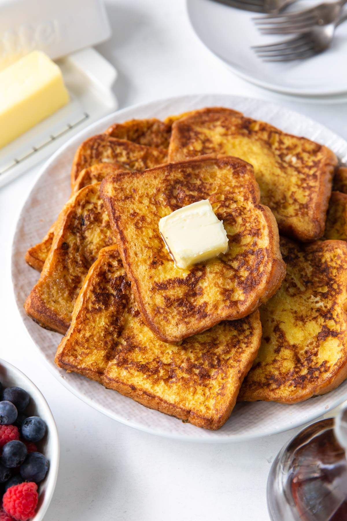 french toast slices piled on a serving plate with butter on top