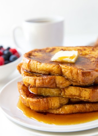 five slices of french toast stacked on a plate served with butter and maple syrup