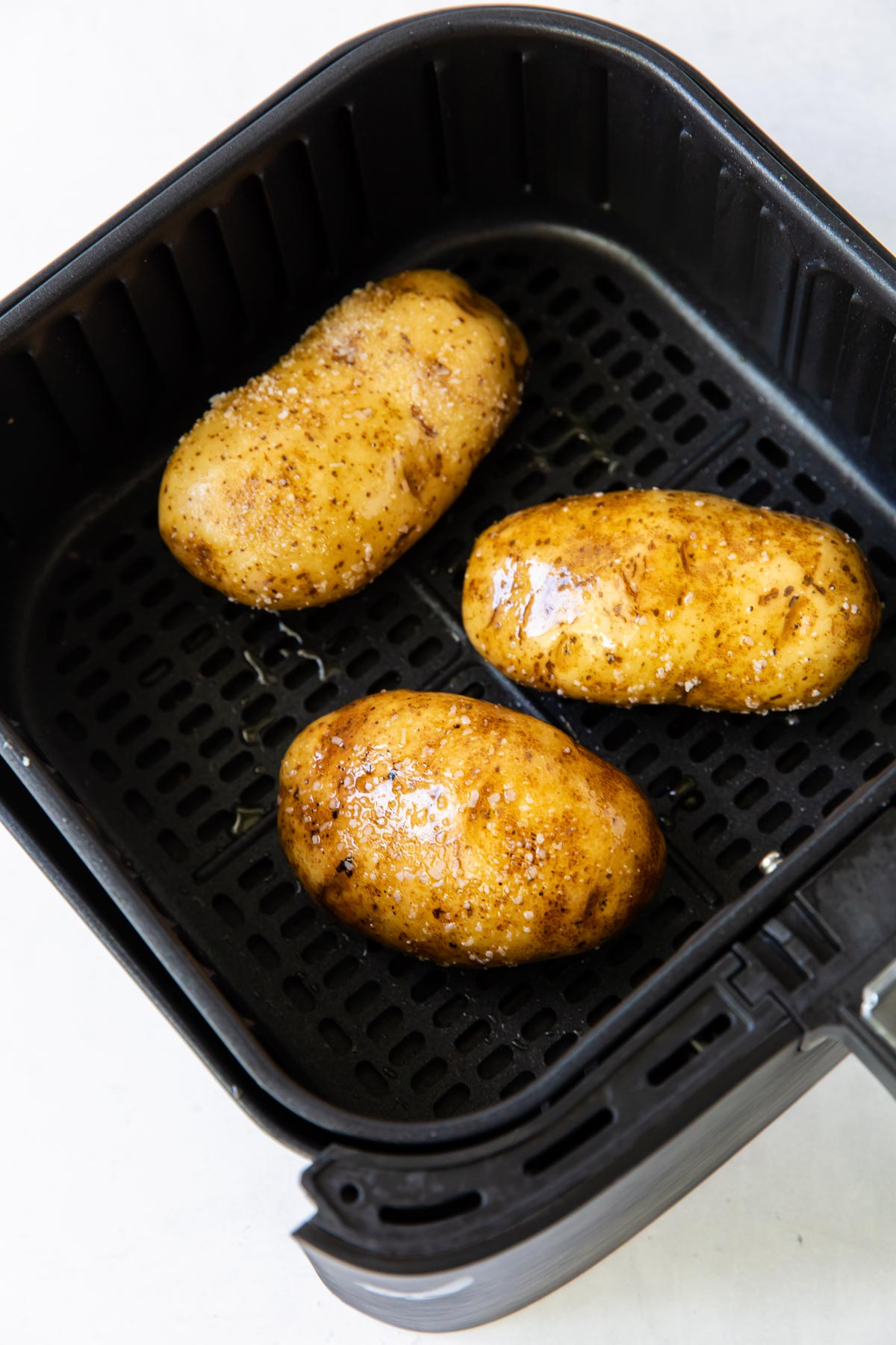 three russet potatoes rubbed with oil and salt in air fryer basket