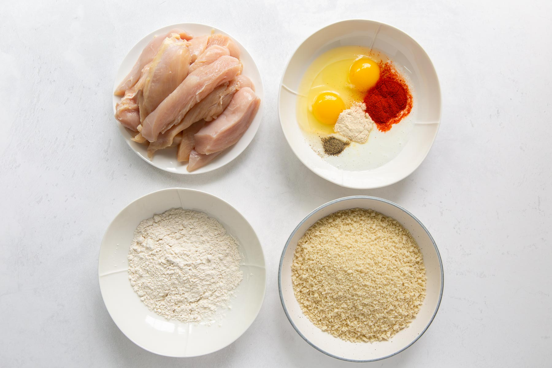 ingredients for chicken tenders, chicken, egg, buttermilk, seasonings, flour and panko breadcrumbs in white dishes