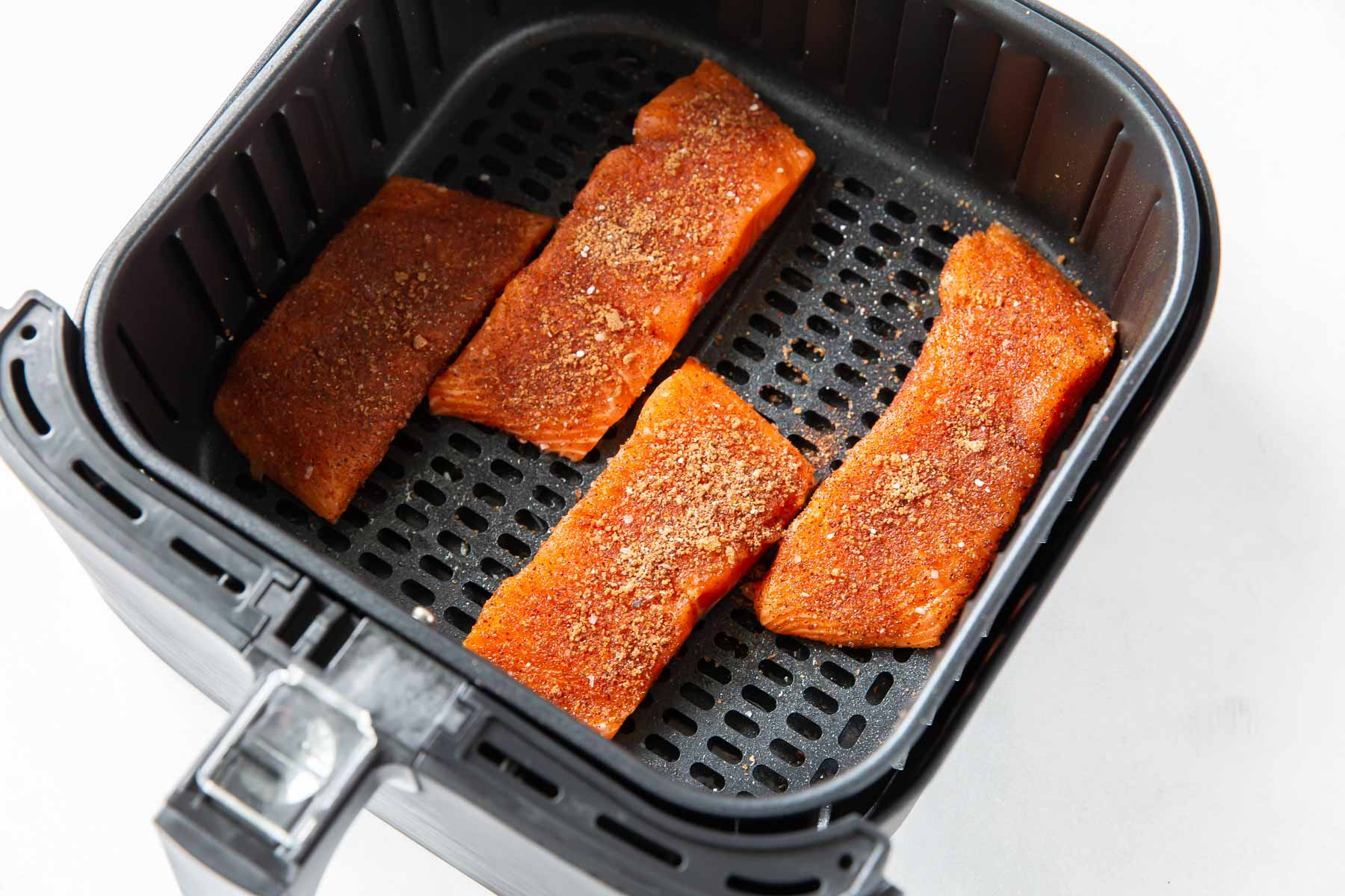 four raw salmon fillets with seasoning in air fryer basket