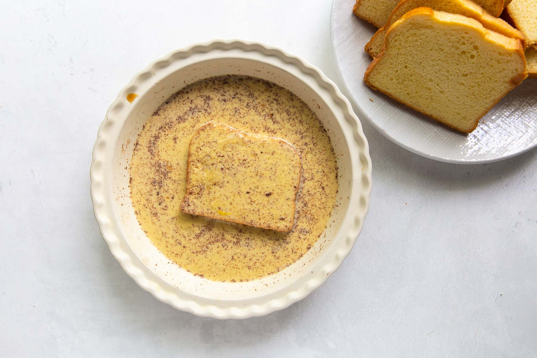 slice of bread soaking in French toast batter