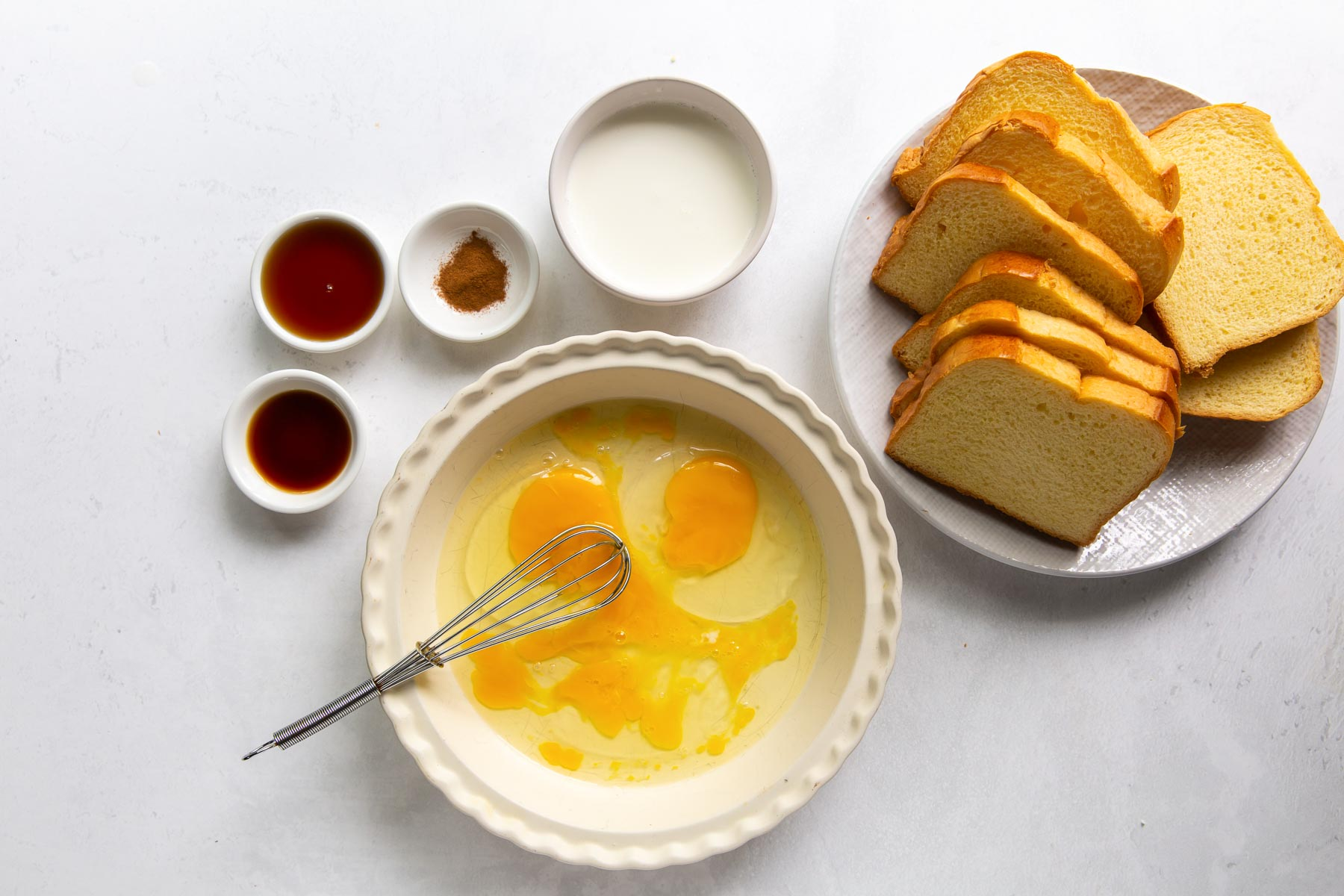 eggs and whisk in a pie plate with other ingredients in background