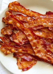 oven baked bacon stacked on a plate