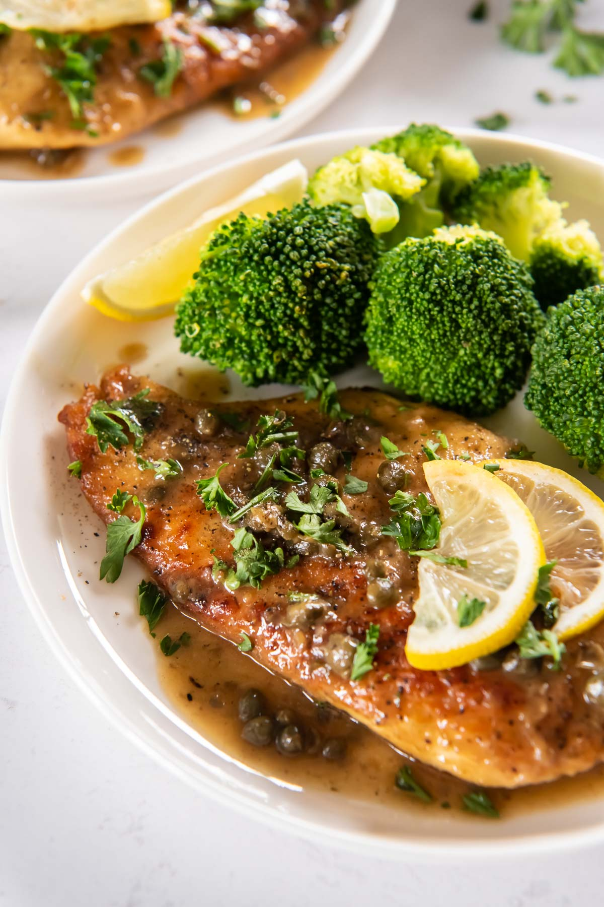 chicken piccata on a plate served with steamed broccoli