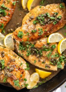 chicken piccata with parsley and lemon wedges in skillet