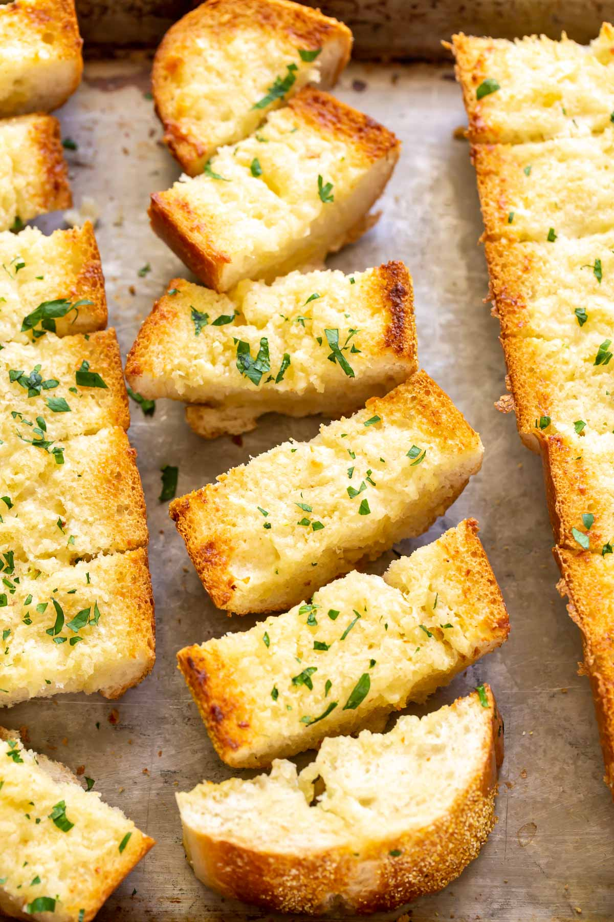 slices of oven baked garlic bread topped with fresh parsley on a baking sheet