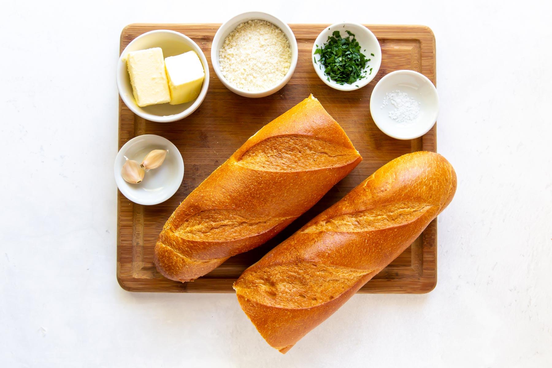 ingredients for garlic bread recipe on a wood cutting board