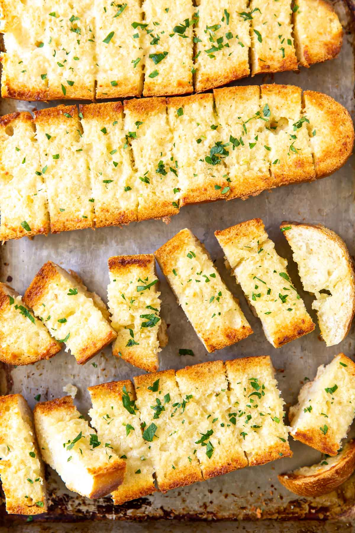 freshly baked garlic bread on baking sheet with some pieces separated and some together in loaf shape