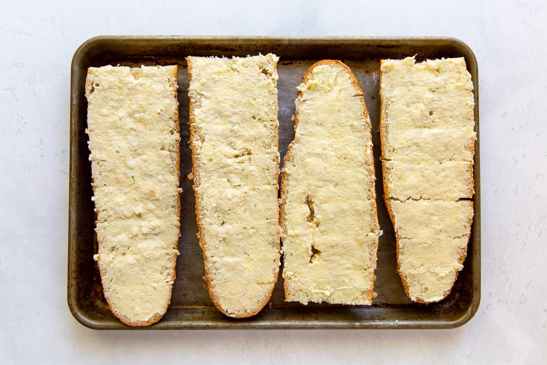 garlic butter spread on french bread on baking sheet