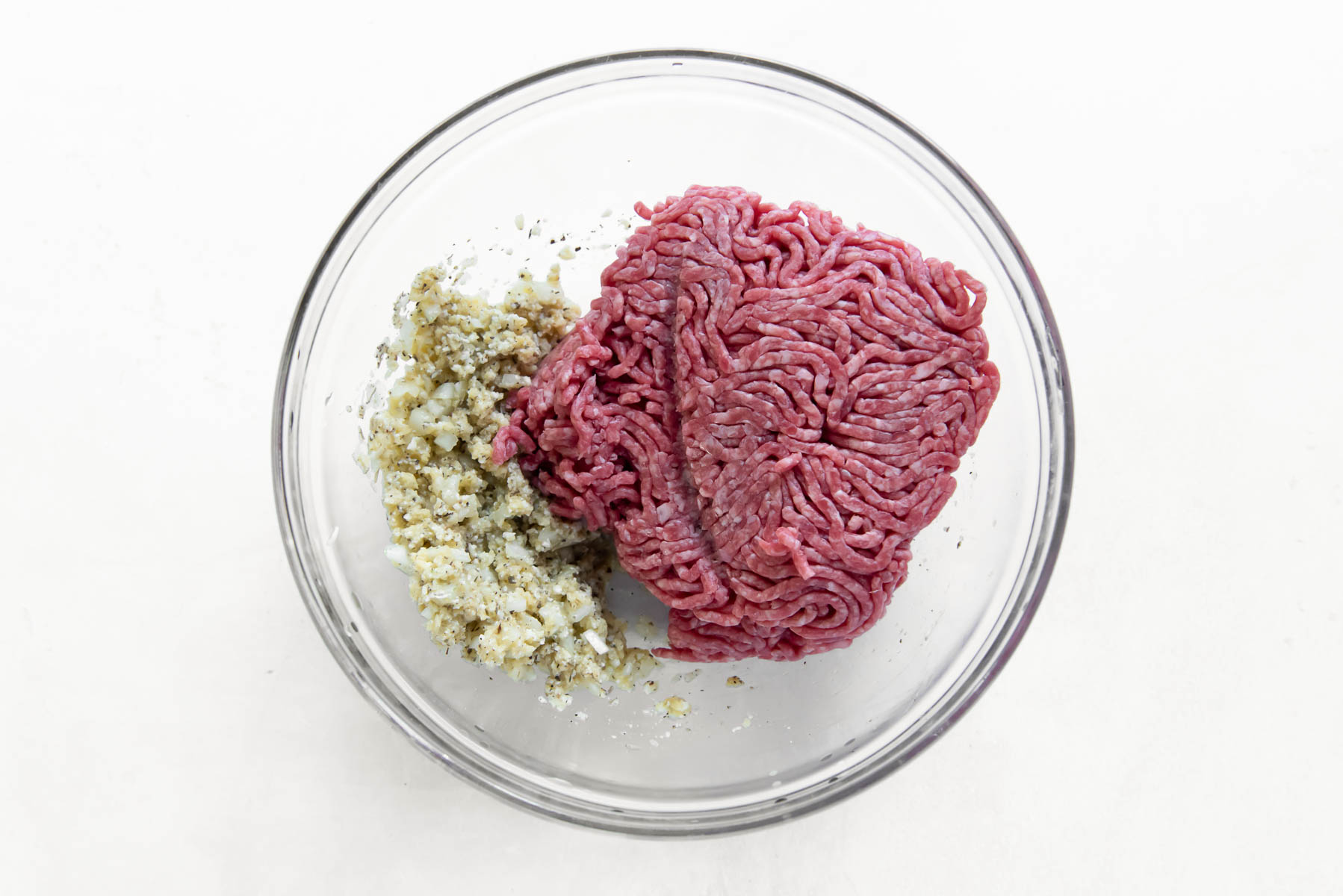 ground beef and other meatball ingredients in a glass bowl