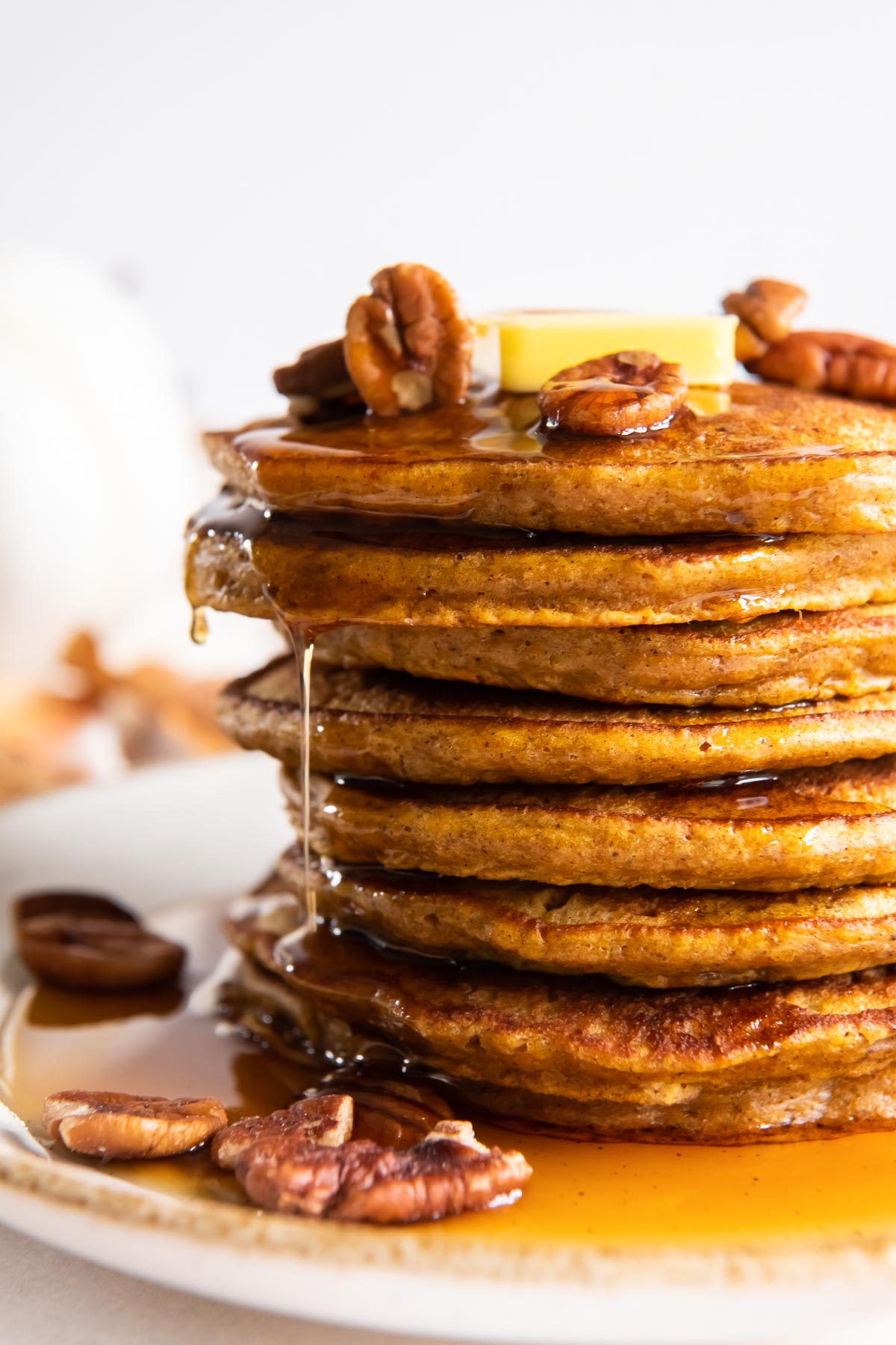 side view of stack of eight pumpkin pancakes with syrup dripping down