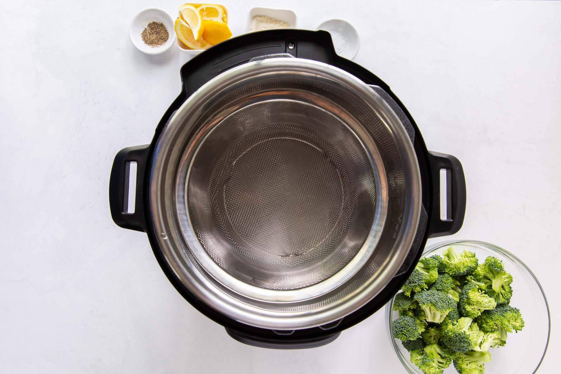 instant pot with water and steamer basket in it