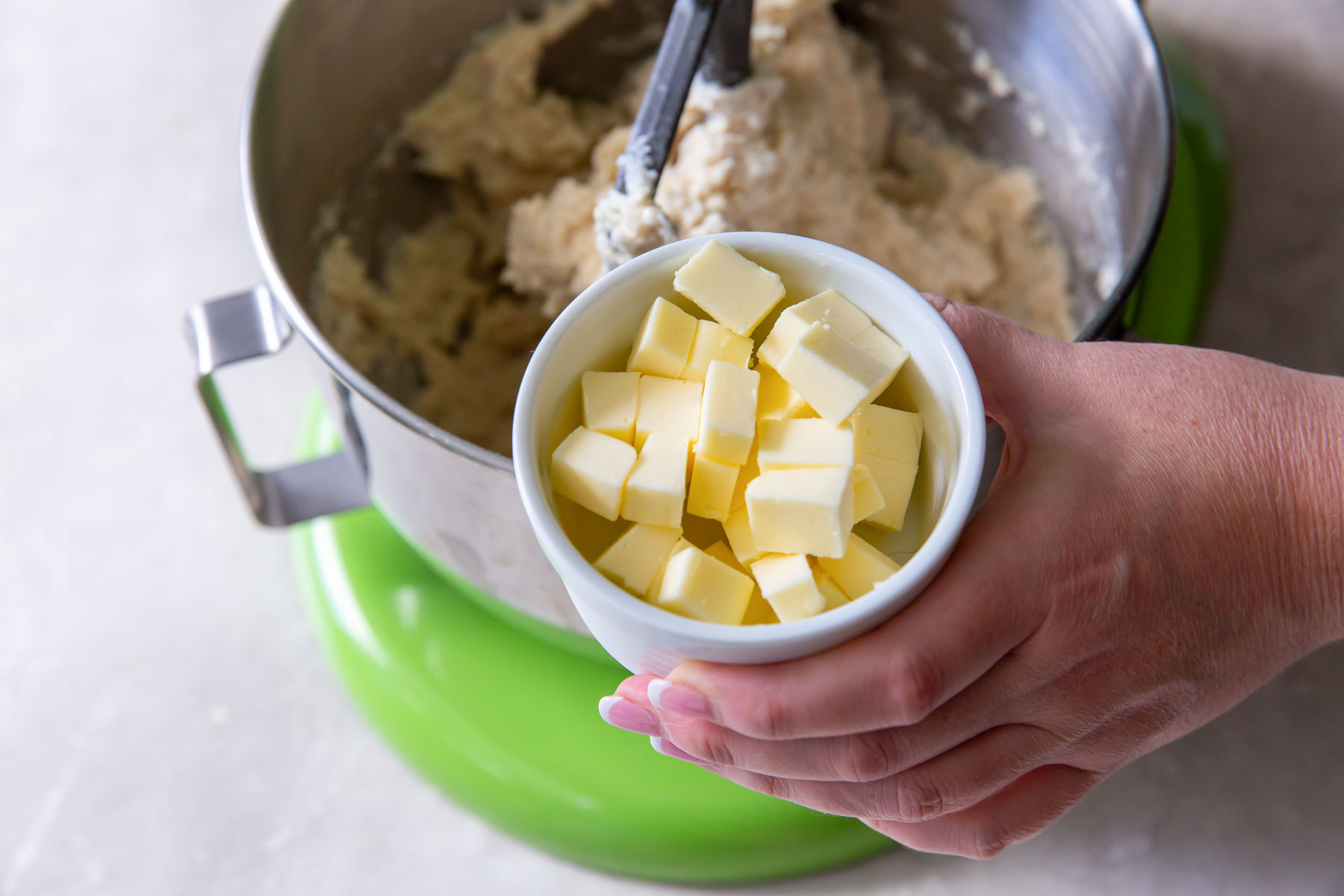 holding small dish of butter cubes in front of mixer with dinner roll dough