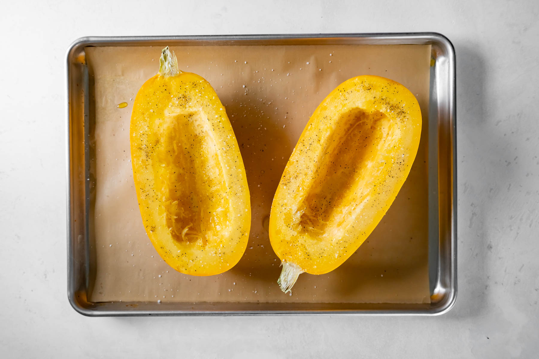 two spaghetti squash halves with olive oil, salt and pepper