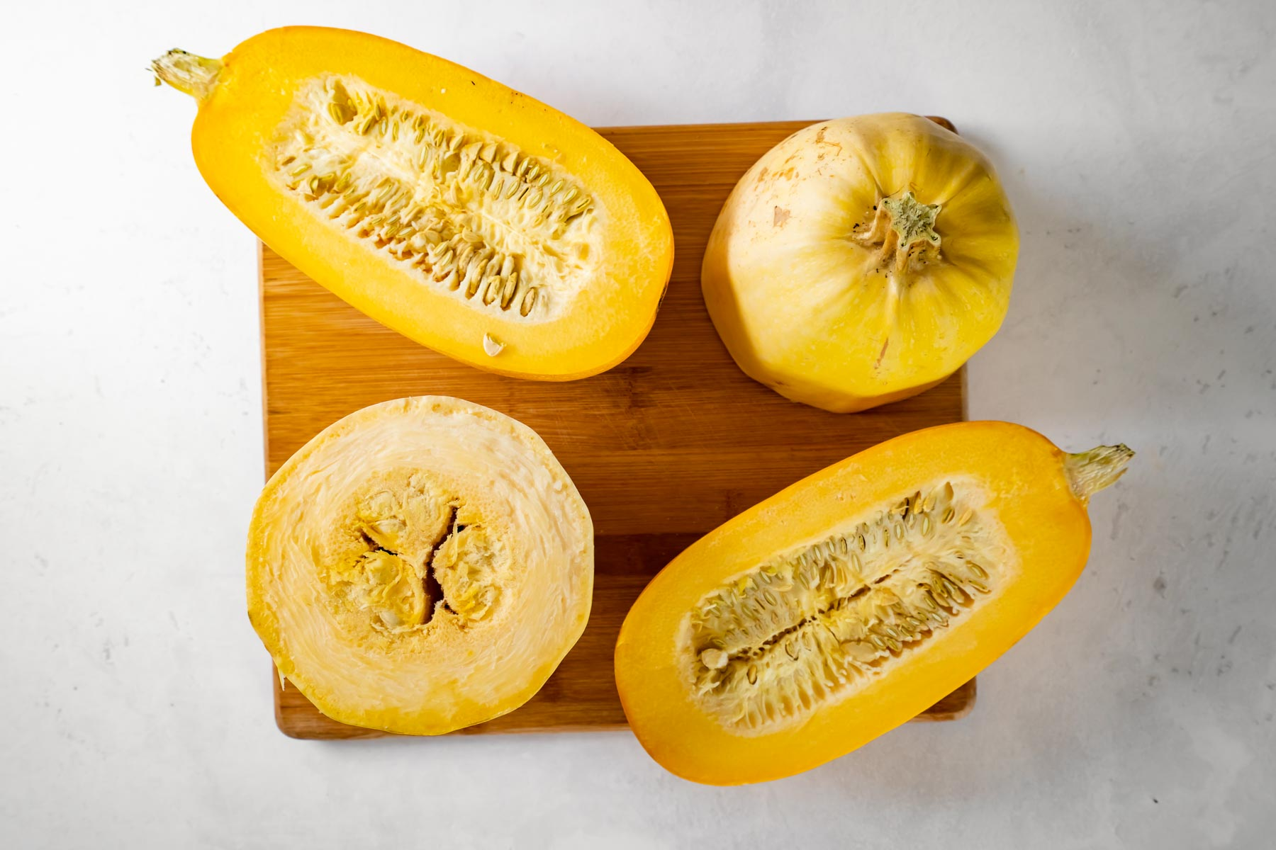 one spaghetti squash cut in half lengthwise and another cut in half crosswise