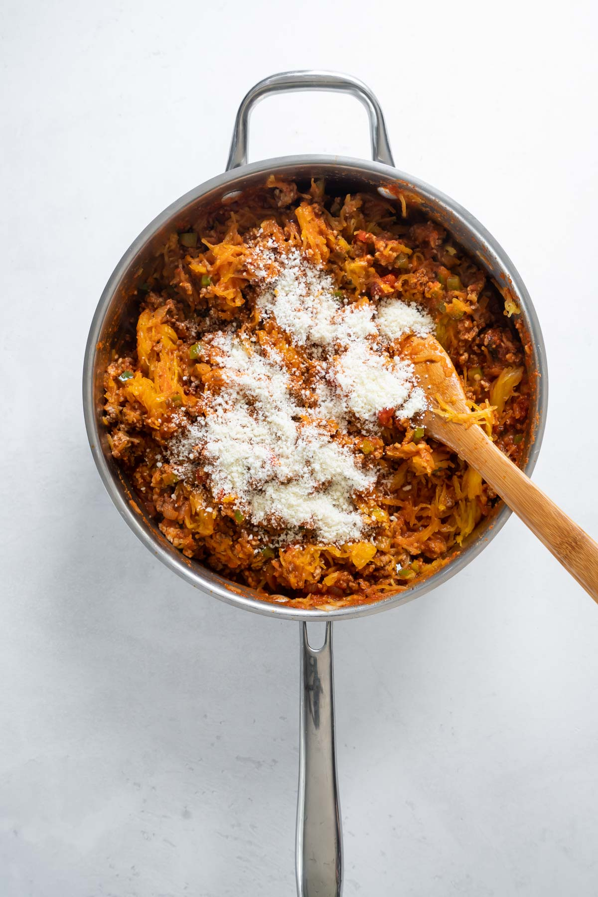 stirring parmesan into spaghetti squash mixture