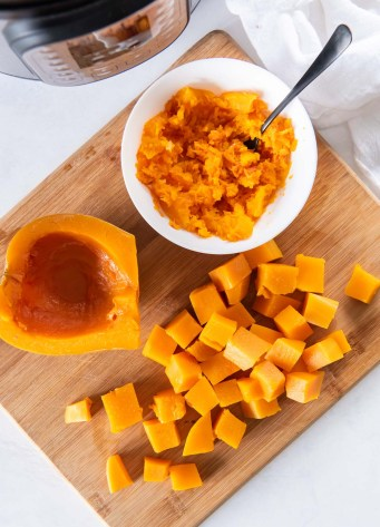 quartered, cubed and mashed butternut squash with instant pot in background