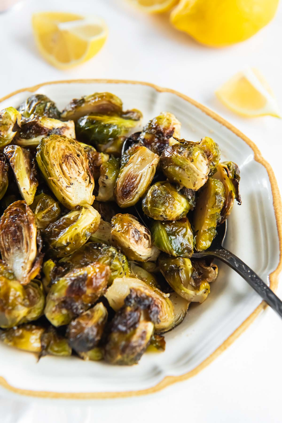 roasted brussels sprouts in a serving dish with a spoon
