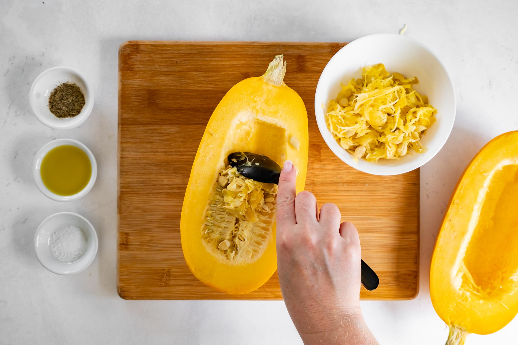 scooping seeds out of spaghetti squash