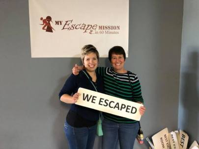 """Caitlin and Me holding sign that reads """"We Escaped"""" at My Escape Mission"""