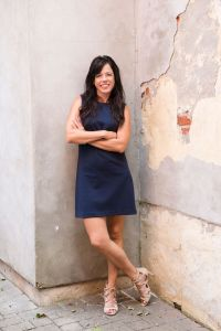 Kristin standing in front of an outdoor wall.  Arms folded, Ankles crossed.