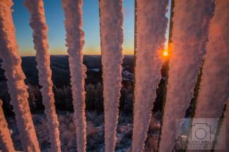 Die Sonne scheint durch das verschneite Gitter am Aussichtsturm