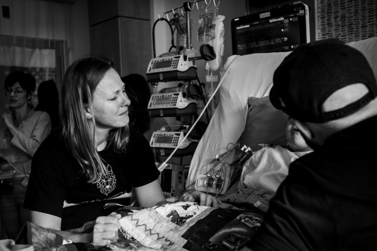 Kristy Wolfe crying while standing over her son's hospital bed following his open heart surgery at the Stollery Children's Hospital. Photo credit Slice of Love Photography