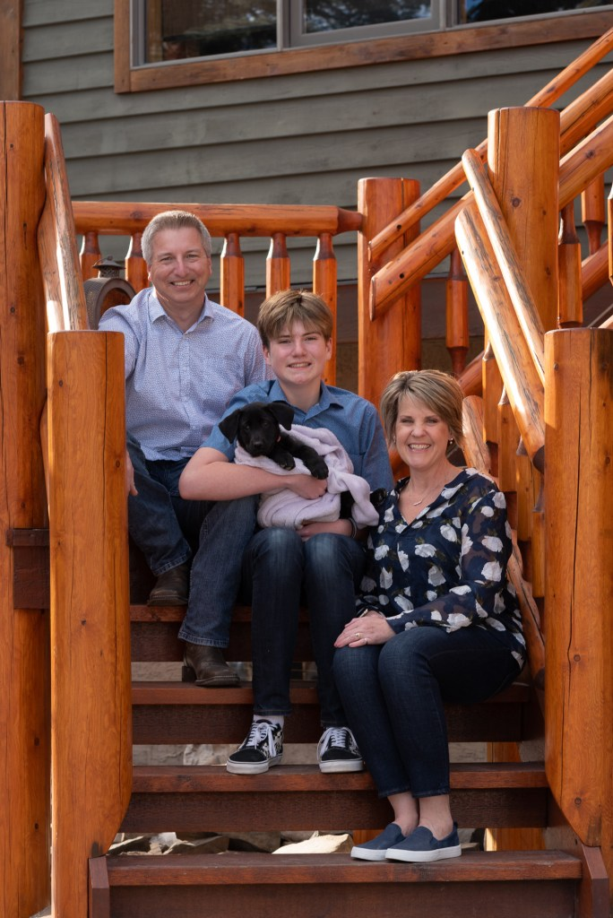 A family of three take part in the Front Steps Project with their new puppy.