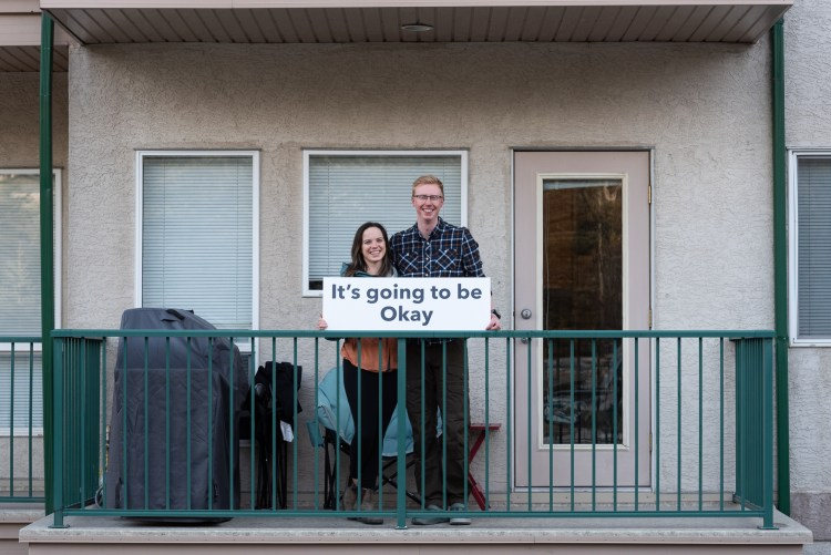 "A couple on their balcony holding a sign that reads ""It's going to be Okay"""