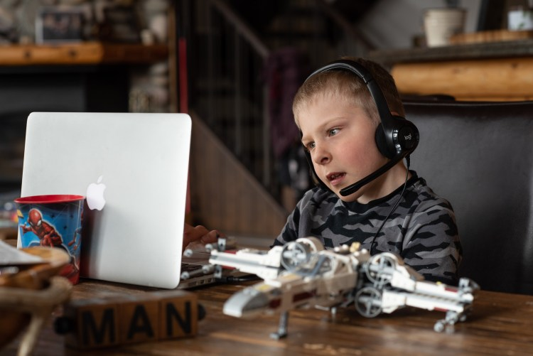 A young boy uses a headset and a computer to talk to his teacher.