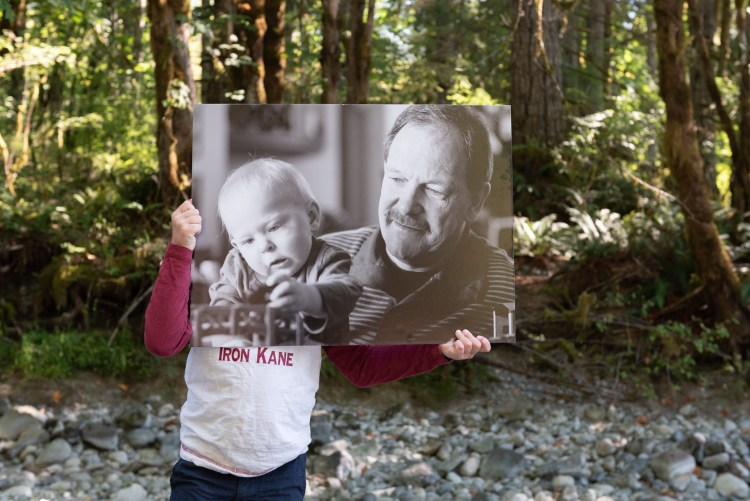 A child holds up a picture of himself and his grandad, a reminder of a loved one who died by suicide.