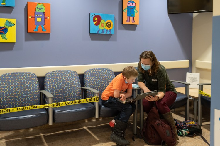 A woman and a child sit in the waiting room of the cardiology clinic at the Alberta Children's Hospital during COVID.  (2021-01-06)