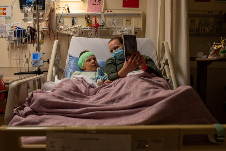 A mother and child read together in a hospital bed.
